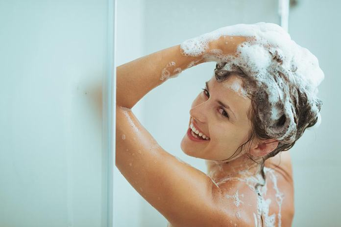 smiling-young-woman-washing-head