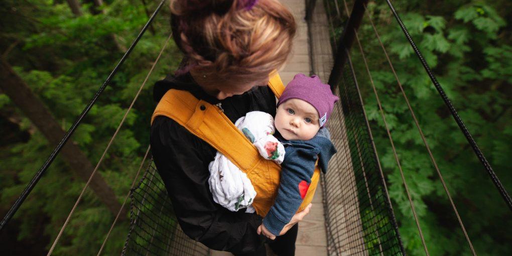 woman-carrying-baby-on-bridge